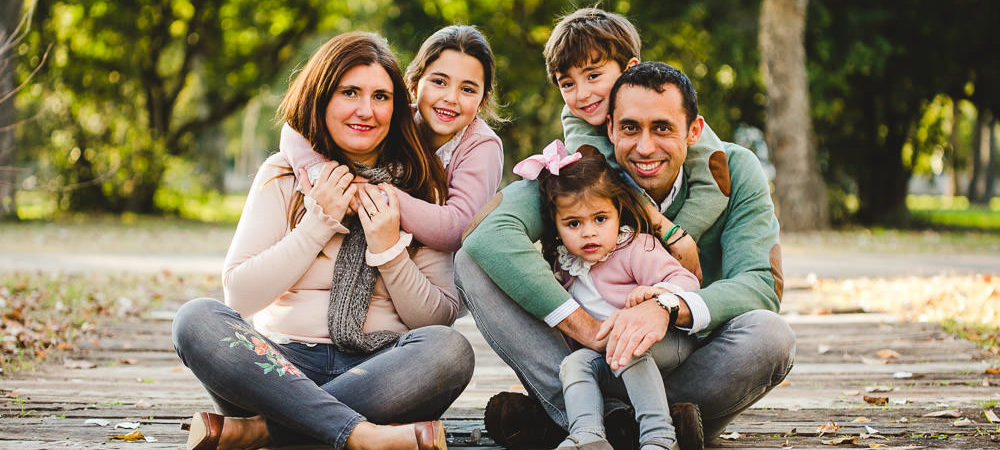 Fotografía de familia en Sevilla. Tres hermanos en el parque.